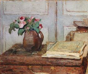 Quiet life with the painting suitcase of the artist and a vase with moss roses