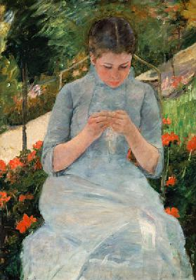 Young knitting woman in the garden