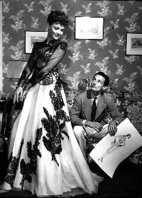 fashion designer Oleg Cassini showing his drawings to Gene Tierney to show her the clothes for film