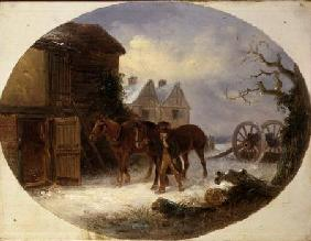 Boy leading horses to a barn in the snow